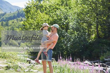 Father and daughter beside stream, Saut Deth Pish, Valle de Aran, Spain