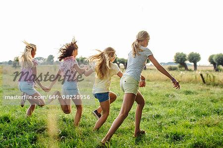 Girls holding hands, running in line, on field, Flanders, Belgium