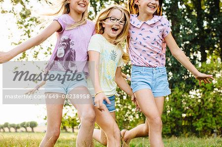 Girls running together on field, Flanders, Belgium