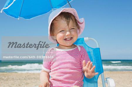 Female toddler wearing sunhat on beach chair