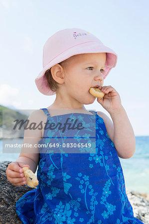 Female toddler wearing sunhat eating doughnut on beach
