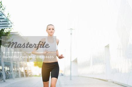 Young female runner running on city sidewalk