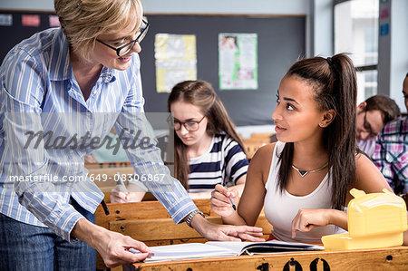 Teacher helping female student in classroom