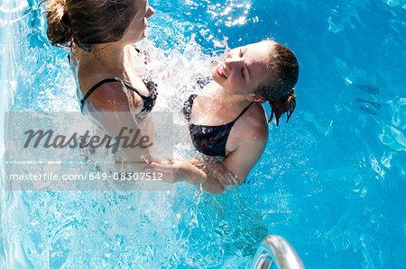 Teenage girls splashing in swimming pool
