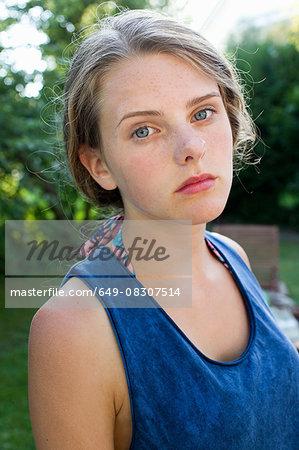 Portrait of sullen teenage girl in garden