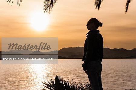 Silhouette of mountain range and mid adult woman under setting orange sun, Majorca, Spain