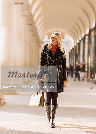Stylish young woman carrying shopping bags, Covent Garden, London, UK