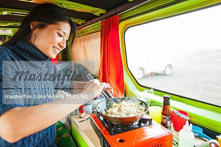 Woman cooking stir fry in camper van, Iceland