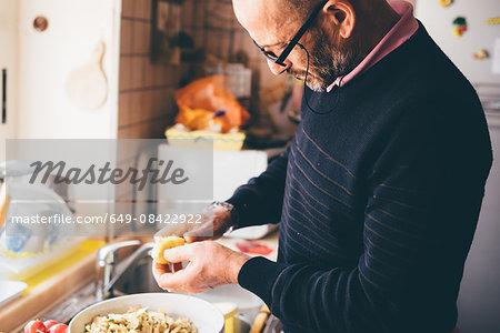 Senior man slicing artichokes in kitchen