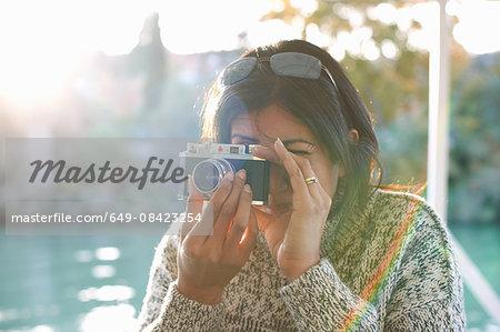 Mature female tourist photographing at Guadalqivir river, Seville, Spain