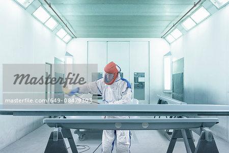 Portrait of worker paint spraying parts on automotive production line