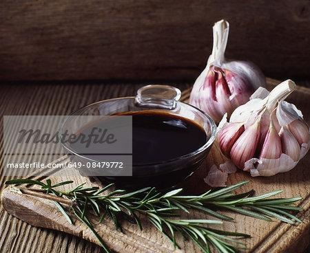 Rosemary, garlic bulbs and bowl of balsamic vinegar