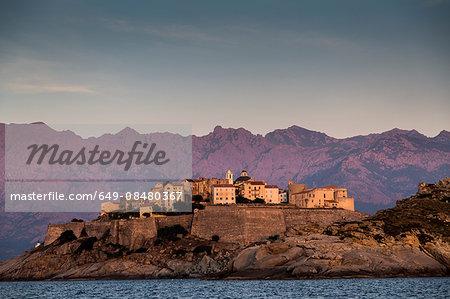 View of sea and Calvi on headland at dusk, Corsica, France