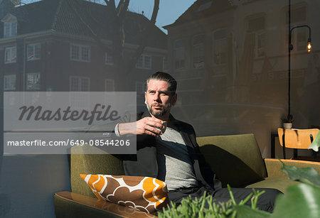 Window view of cool man sitting on retro cafe sofa looking through window