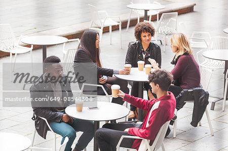 Friends sitting at tables at sidewalk cafe enjoying a coffee