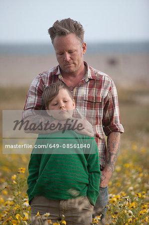 Man hugging son in field of flowers