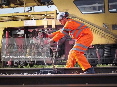 Railway maintenance worker tightening bolts on track
