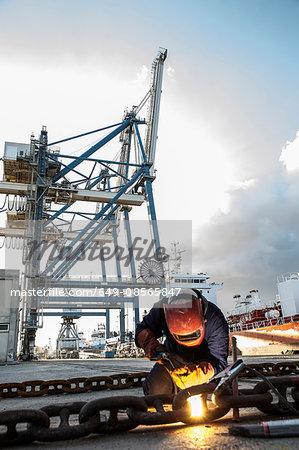 Dock welder welding chain on pier