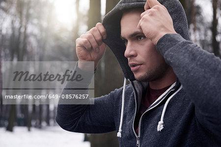 Young man wearing hooded sweatshirt, in snowy, rural landscape
