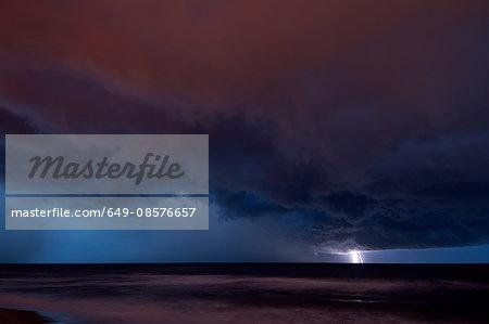 Distant lightning hitting water over the Atlantic Ocean, at night, near Satellite Beach, Florida, USA