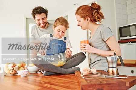 Girl whisking eggs on kitchen counter for parents breakfast