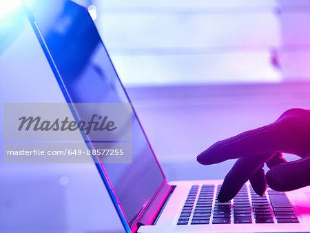 Gloved hand hacking laptop computer
