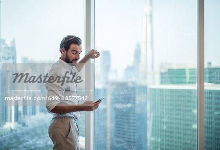 Businessman reading smartphone text at window with view of Burj Khalifa, Dubai, United Arab Emirates