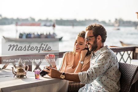 Romantic couple reviewing camera at Dubai marina cafe, United Arab Emirates