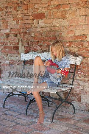Girl sitting on bench playing ukulele, Buonconvento, Tuscany, Italy