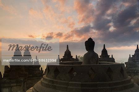 Silhouetted buddha, The Buddhist Temple of Borobudur, Java, Indonesia
