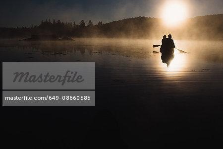Senior couple canoeing on lake at sunset