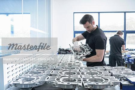 Engineer working on part in racing car factory