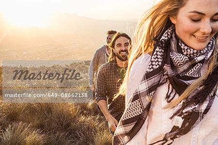 Friends rambling on grassland smiling