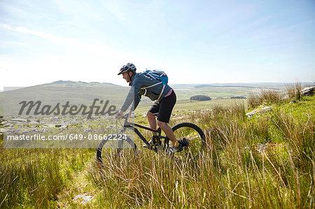 Cyclist cycling on hillside