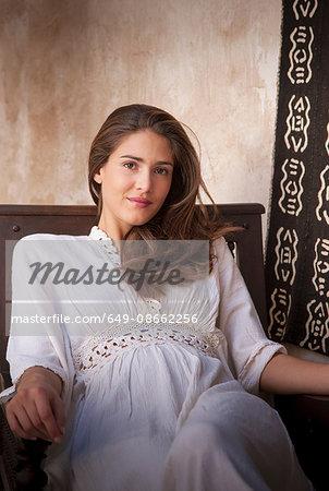 Portrait of woman wearing kaftan sitting in chair, Marrakesh, Morocco