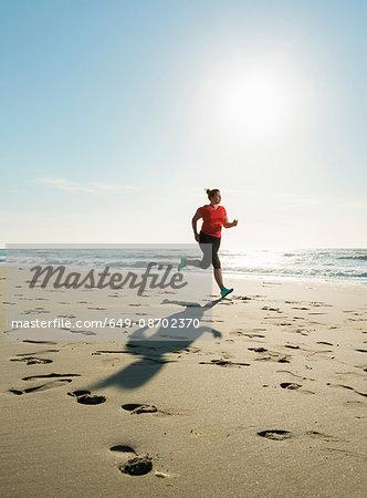 Mature woman running on a beach at sunset