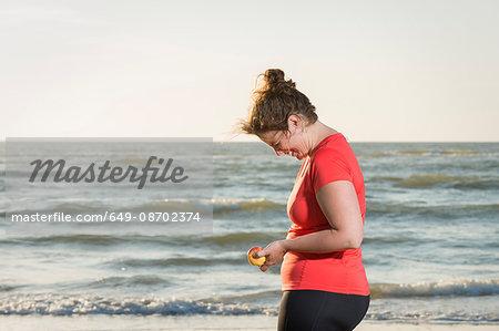 Mature female runner standing on beach at sunset, laughing