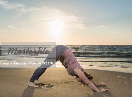 Mature woman practising yoga on a beach at sunset, downward facing dog pose