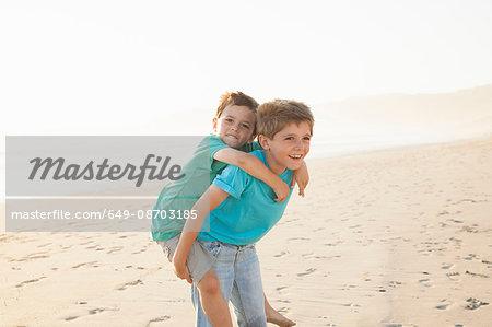 Boy giving brother piggyback on beach
