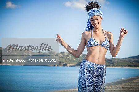Beautiful young woman wearing bikini top and sarong dancing on beach, Costa Rei, Sardinia, Italy