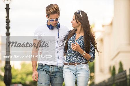 Young couple strolling along street, London, UK