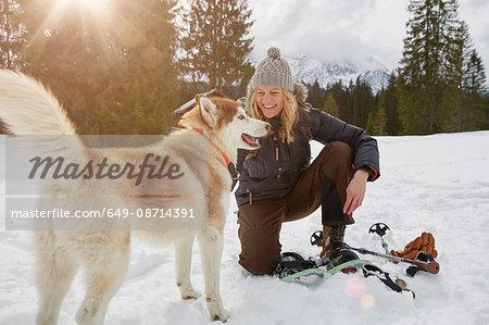 Mature woman crouching by beside dog in snowy landscape, Elmau, Bavaria, Germany