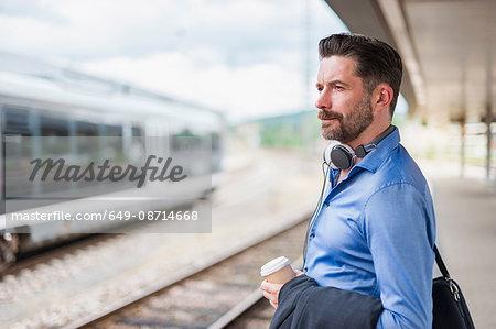 Mature businessman with takeaway coffee on railway platform
