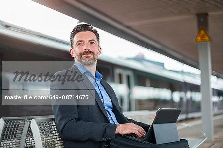 Mature businessman typing on laptop on railway platform