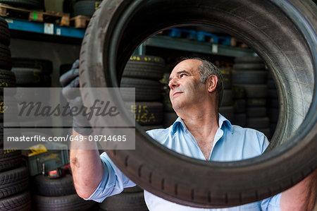 Senior male business owner mechanic examining tyre in repair garage