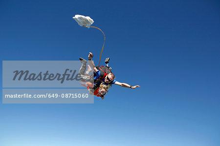 Tandem sky divers free falling with parachute opening, Interlaken, Berne, Switzerland