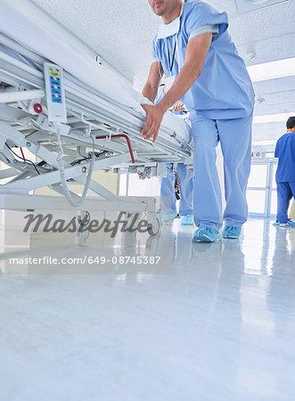 Two medics urgently pushing hospital bed along corridor