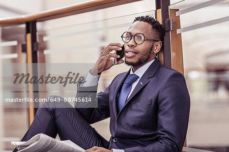 Businessman sitting on floor chatting on smartphone on office balcony