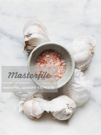 Garlic bulbs and pink sea salt in bowl
