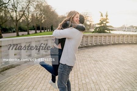 Romantic young man hugging girlfriend in Battersea Park, London, UK